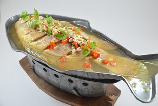 Steamed whole fish with lemon sauce.